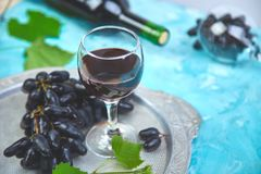 Red wine concept with bottle, glass and grapes. On silver tray on blue background, copy space. Wine header image. Wineglasses royalty free stock image