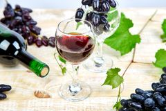 Red wine concept with bottle, glass and grapes. On wooden background. Wine header image. Wineglasses stock photo