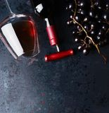 Red wine concept. Glass with red wine, bottle and red grape clusters on black rustic background, top view. Stock Photography