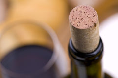 Red wine and cork. Close-up of wine bottle with cork. glass with red wine. The top of the bottle and the cork are in focus, the glass in background is blurred stock photo