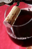 Red Wine and Cork. Red wine in glass with cork and corkscrew. Focus is on the cork Royalty Free Stock Photo