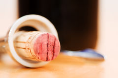 Red wine cork in corkscrew in front of a wine bottle Stock Photography