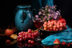 Red wine, dark blue jug and fruit on a black background. Still-life with wine, fruit and a dark blue jug on a black background Royalty Free Stock Photo