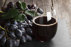 Red wine and dark grapes on a wooden background Royalty Free Stock Images