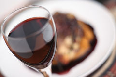 Red wine dinner; soft focus wide view. Red wine in a glass with shallow depth of field and soft focus, in front of a meal with a rich, red wine sauce Stock Image