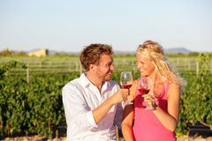 Red wine drinking couple toasting at vineyard. People drinking red or rose wine smiling happy doing toast. Romantic lovers outside. Young Caucasian men and Royalty Free Stock Photos