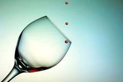 Red wine droplets falling in a glass cup Royalty Free Stock Image