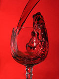 Red wine. Enters glass in red bacground Stock Photo