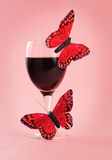 Red wine and fake butterflies Stock Images