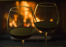 Red Wine by the Fire. Two glasses of red wine with reflections from a nearby fireplace Stock Photos