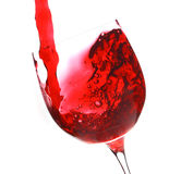 Red wine flow in a wineglass. On white background Stock Photo