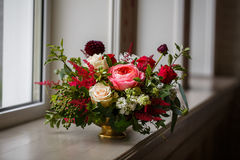 Red wine flower arrangement. In the restaurant with large windows Royalty Free Stock Images