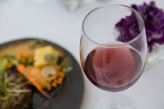 Red wine with food served on table in restaurant Stock Photos