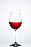 Red wine in the fragile pure wineglass standing against light bckground with reflection. Stock Photo
