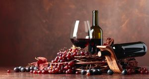 Red wine and fresh grapes with dried up vine leaves. Red wine and fresh grapes with dried up vine leaves, copy space for your text stock image