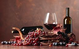 Red wine and fresh grapes with dried up vine leaves. royalty free stock photography