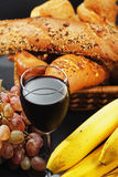 Red wine among fruits and pastry Royalty Free Stock Image