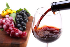 Red wine and fruits. Pouring red wine into glass and fruits Royalty Free Stock Photos