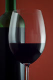Red wine glass. Photo of a wine glass, with a bottle on a background Stock Photography