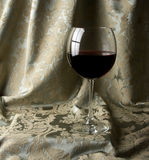 Red Wine in a Glass. Red Wine with a green damask draped background royalty free stock images