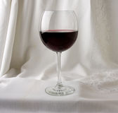 Red Wine in a Glass. Glass of Red Wine with a white damask draped background stock photography