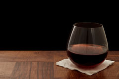 Red wine glass. Steamless glass of red wine on a bar top isolated on a black background royalty free stock photos