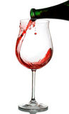 Red wine glass. Red wine being poured into a wine glass, drop sparks of red wine Royalty Free Stock Image