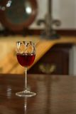 Red wine in glass. Crystal glass on a dining room table. Focus is on the glass Stock Photography