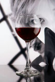 Red wine glass against black and white girl poster. Sight through the glass. Noir style concept Stock Image