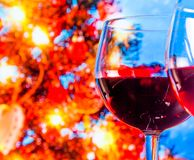 Red wine glass against blur lights tree background. Christmas atmosphere Stock Images