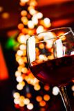 Red wine glass against christmas lights decoration background Royalty Free Stock Image