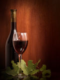 Red wine glass and Bottle. On a wooden background royalty free stock image