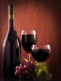 Red wine glass and Bottle. On a wooden background stock images