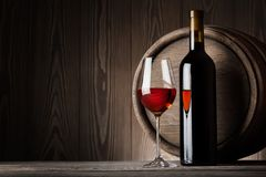 Red wine in glass with bottle. On the background of wooden barrels Royalty Free Stock Photos