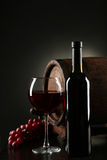 Red wine glass with bottle and barrel on a black background Stock Photos