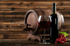 Red wine glass with bottle and barrel on brown wooden background Stock Photography