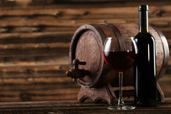 Red wine glass with bottle and barrel on brown wooden background Royalty Free Stock Image
