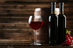 Red wine glass with bottle and barrel on brown wooden background Royalty Free Stock Photography