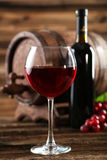 Red wine glass with bottle and barrel on brown wooden background Royalty Free Stock Photo