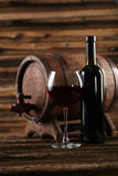 Red wine glass with bottle and barrel on a brown wooden background Stock Images