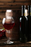 Red wine glass with bottle and barrel on a grey wooden background Stock Photos