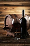 Red wine glass with bottle and barrel on wooden background Royalty Free Stock Photo