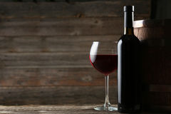 Red wine glass with bottle and barrel on wooden background Stock Photo