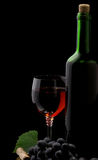Red wine in glass and bottle on black Royalty Free Stock Image