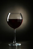 Red wine glass with bottle on a black background Stock Images