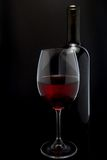 Red wine glass and a bottle in black background Royalty Free Stock Photos