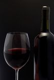 Red wine glass and a bottle in black background Royalty Free Stock Photo