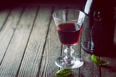 Red Wine glass. And a bottle on dark wooden background royalty free stock photos