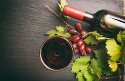 Red wine glass and bottle and fresh grapes on black background, focus on the wine glass royalty free stock image