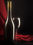Red wine glass and bottle on a silk background. Low key still life. Red wine glass and bottle on a silk background royalty free stock image